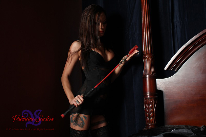 Dominant woman takes charge of the situation with her riding crop during a boudoir photo shoot at Valentine Studios.
