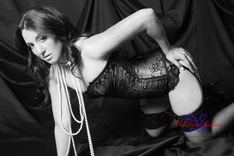 This gorgeous beauty is posing in corset and pearls for a boudoir photo shoot at Valentine Studios.
