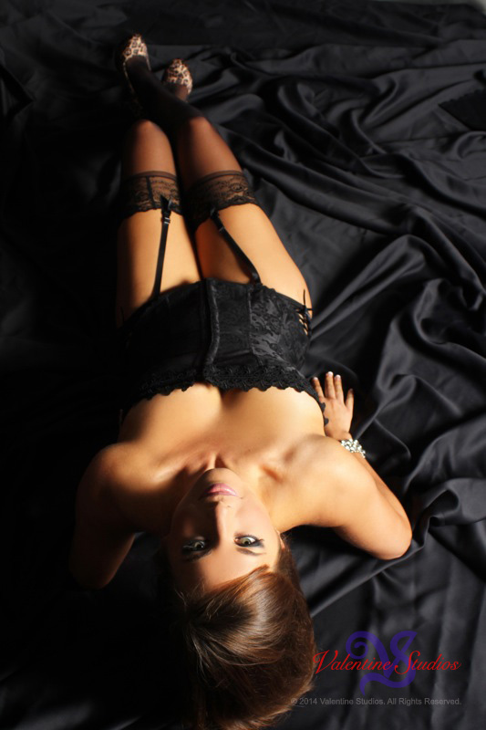 Sexy brunette pose in her black corset, garters and stockings for her boudoir photo shoot.